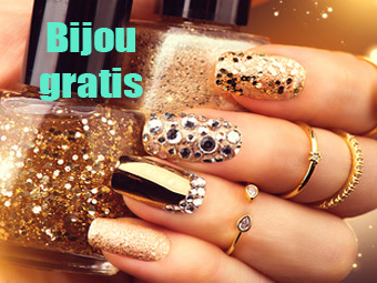 Golden manicure with gems and sparkles. Bottle of nailpolish, tr